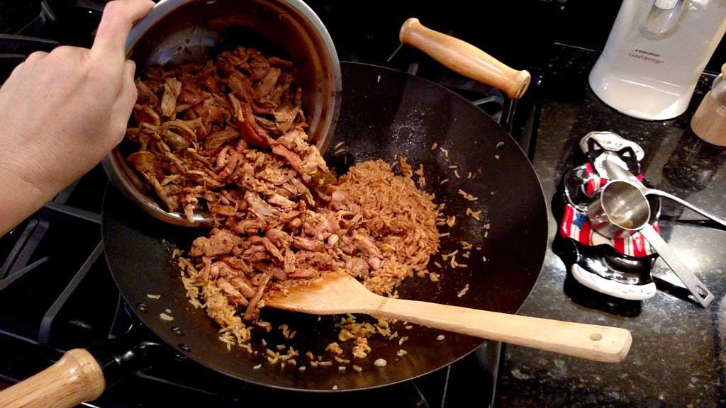 adding orange ginger chicken to wok