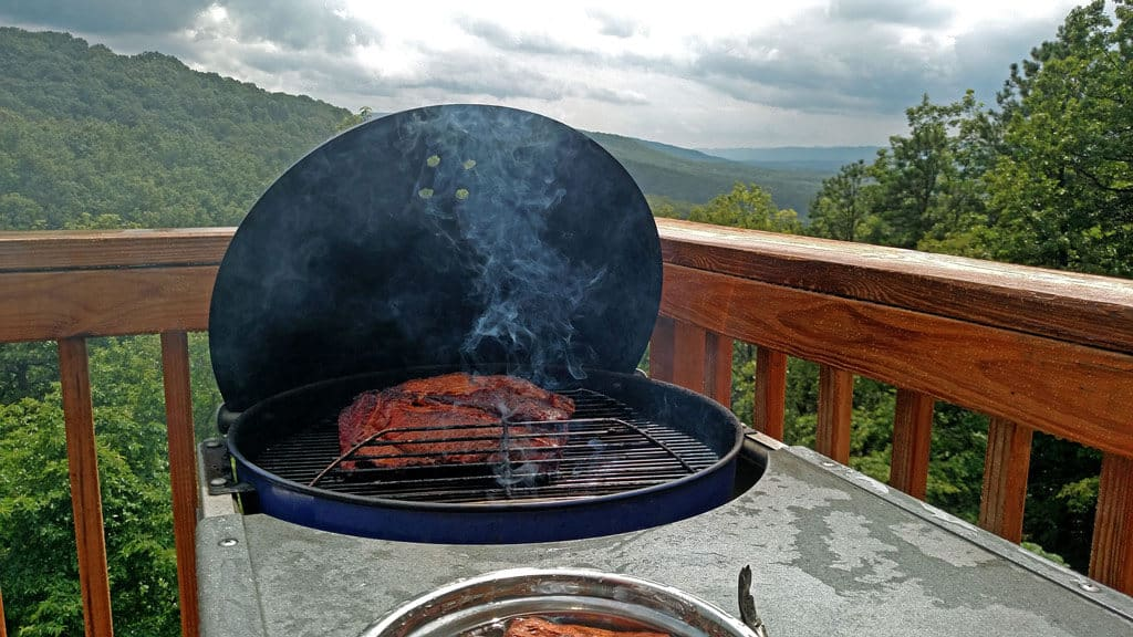 brisket smoking on grill with mountain view