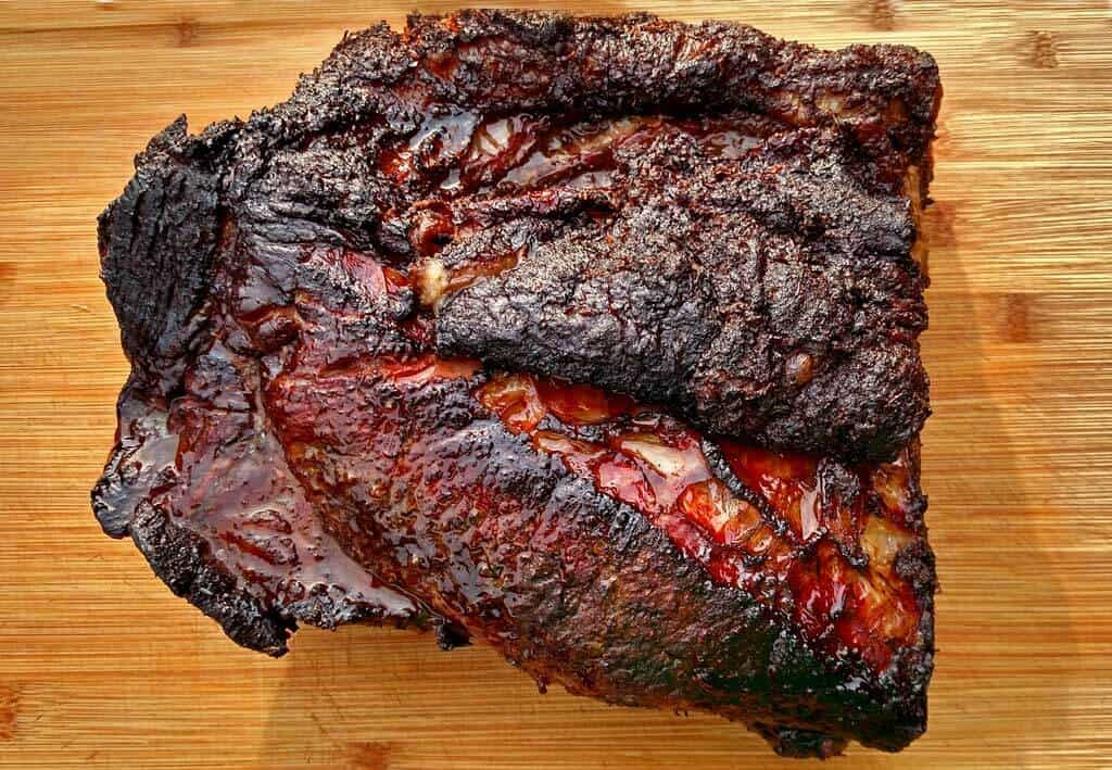 """Low and slow is the key to perfectly smoked beef brisket with crusty """"bark"""" and pink smoke ring. Learn to smoke a brisket on a charcoal grill!"""