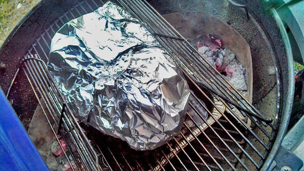 brisket wrapped in aluminum foil on grill