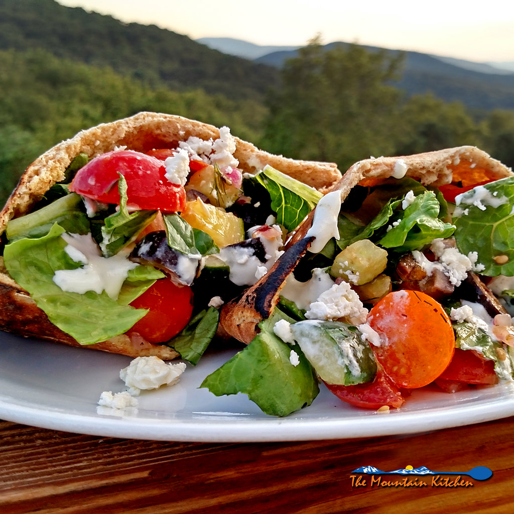 Greek pita sandwiches on plate with mountain view