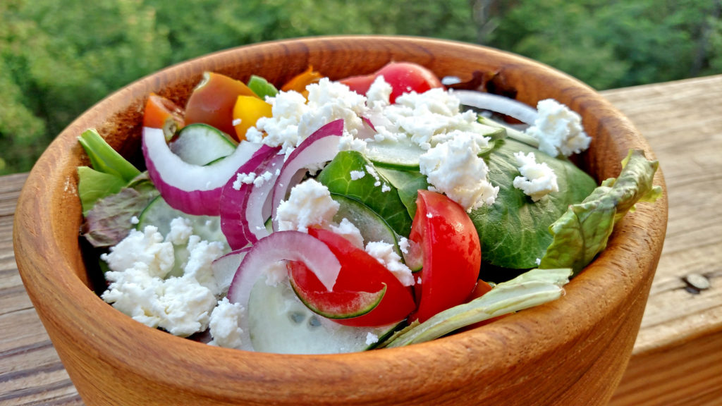 Greek salad made of tomatoes, cucumber, sliced red onion, feta cheese and black olives on a bed of fresh salad greens and drizzled with Greek dressing. | TheMountainKitchen.com