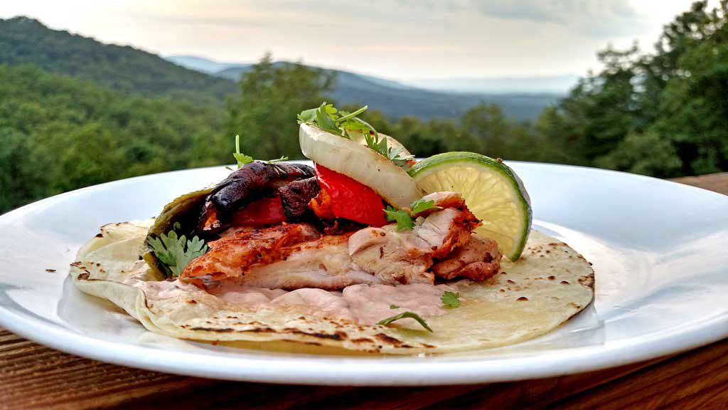 grilled chicken fajitas on plate with tortilla and lime slices