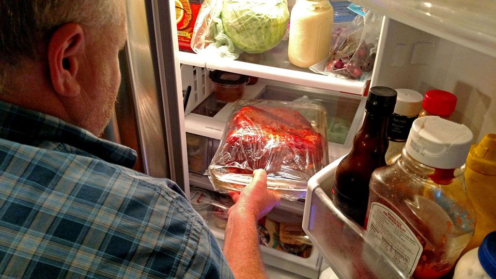 David putting pork in refrigerator