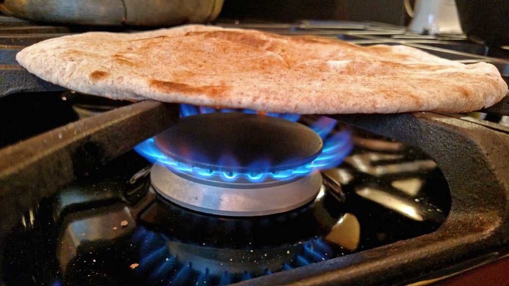 pita bread warming over gas flame on stove