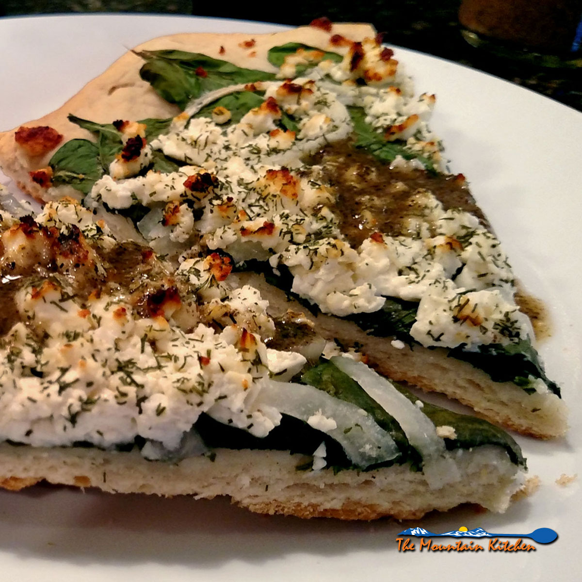 This is spinach feta pizza is topped with spinach, onions, delicious and tangy feta cheese and dusted with fennel, then drizzled with Greek dressing.