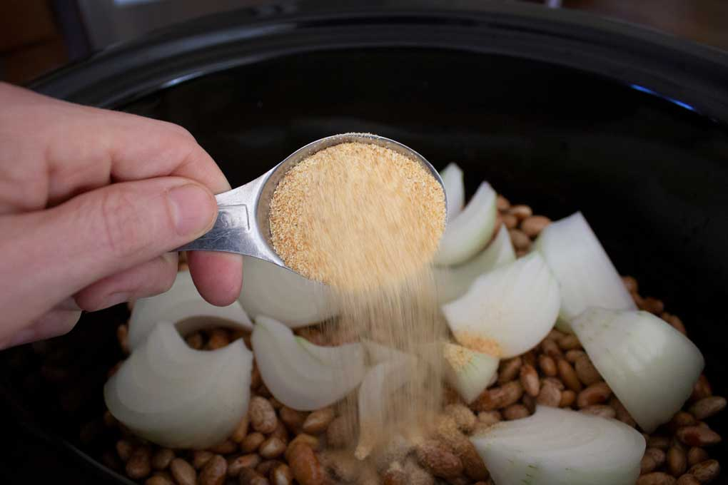 adding garlic to crock-pot of beans
