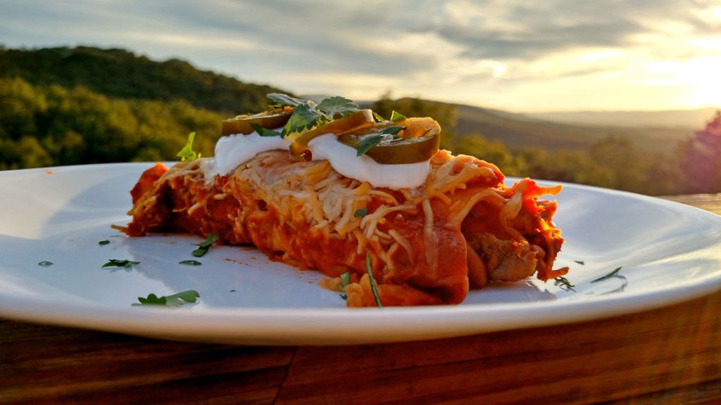 Steak and Refried Bean Enchilada on plate with mountain view