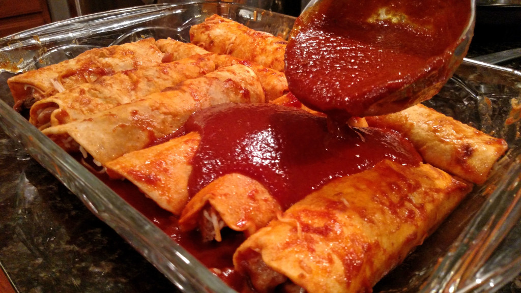 pouring sauce over steak and refried bean enchiladas