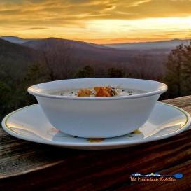 bowl of crock-pot potato leek soup with mountain view