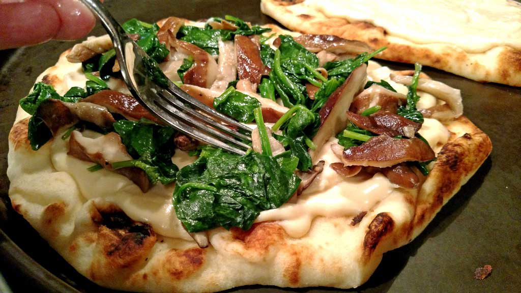 topping the Alfredo covered flatbread with spinach and mushrooms