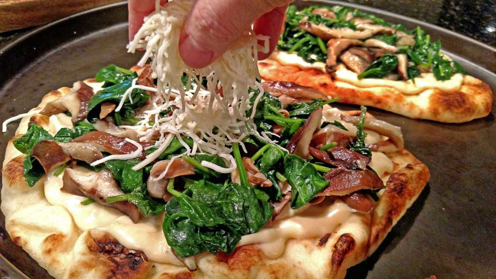 topping the pizza with cheese