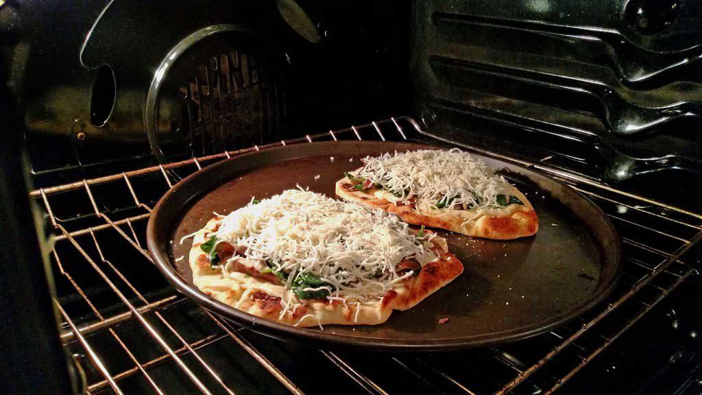 mushroom spinach Alfredo flatbread pizza in oven