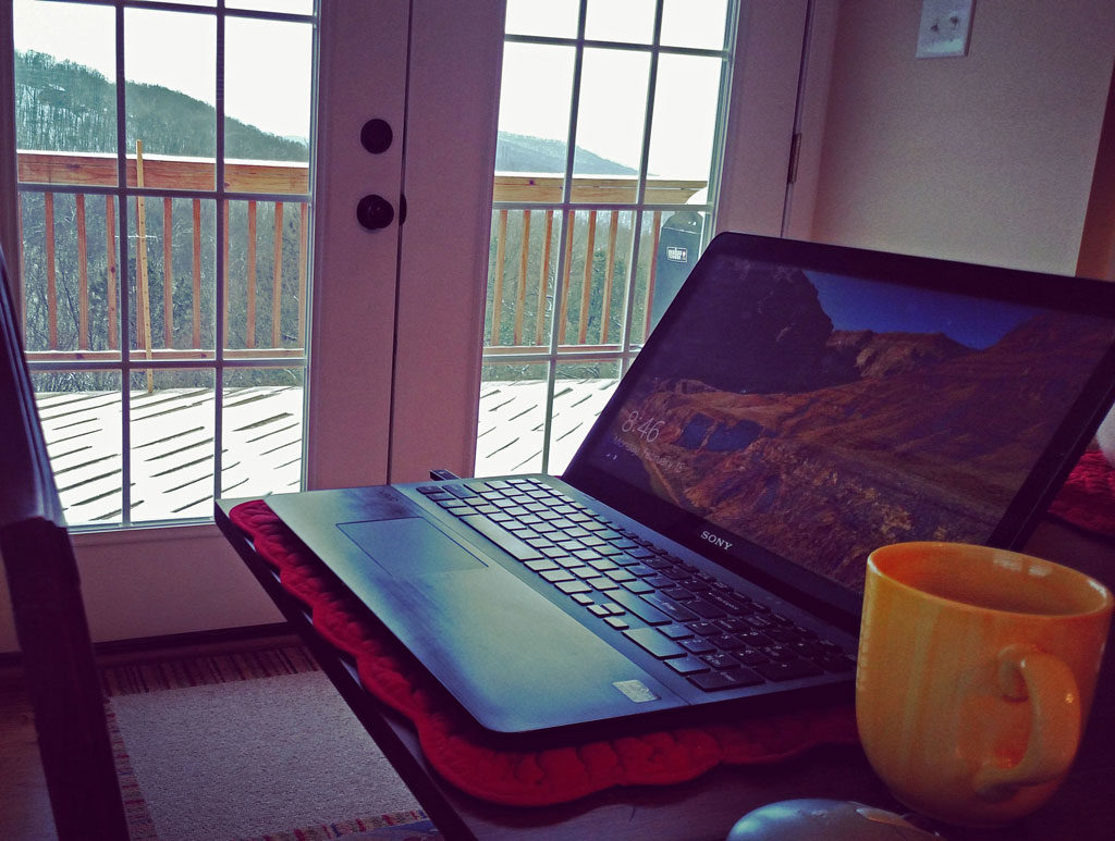 laptop on table with snow outside window
