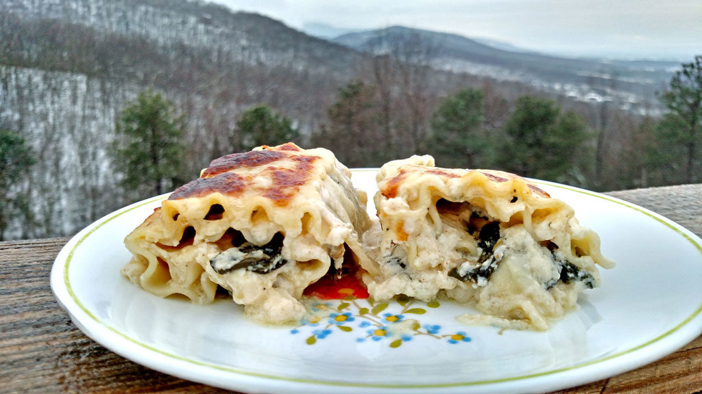 Spinach Artichoke and Mushroom Rollatini on plate with mountain view