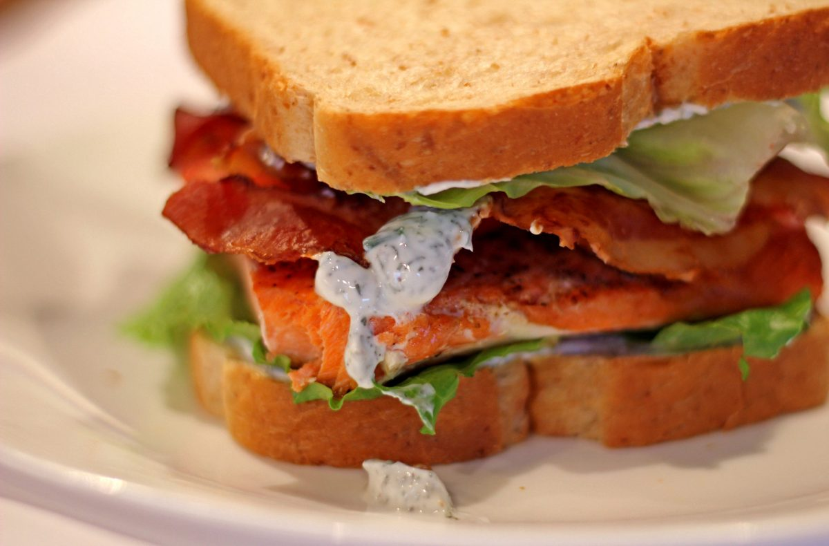 salmon blt sandwich with yogurt dill sauce dripping on plate