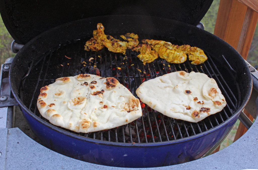naan bread cooking on grill with tandoori chicken