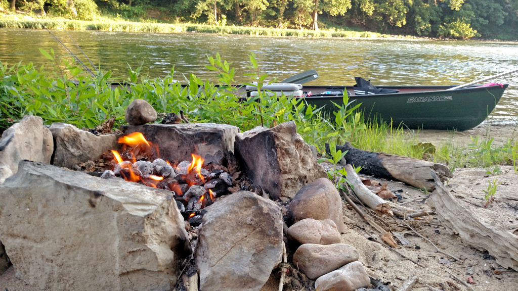canoe by river with camp fire on the bank