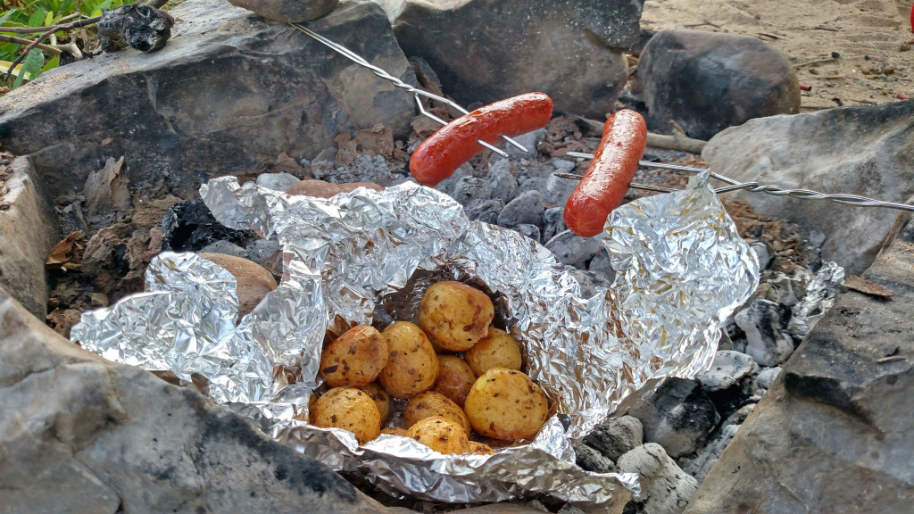 hot dogs and potatoes over camp fire