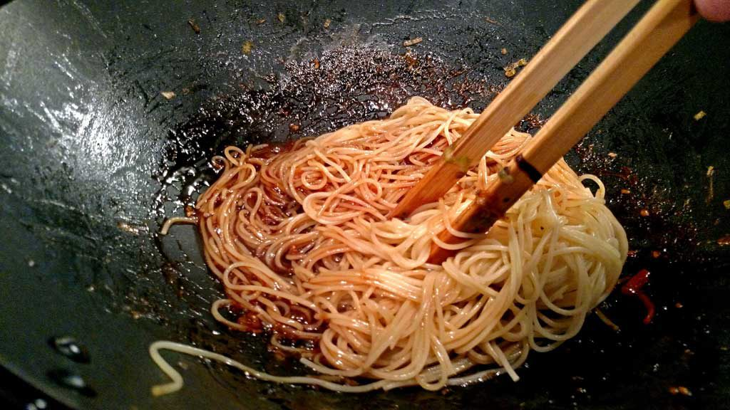 pasta cooking in wok with sauce