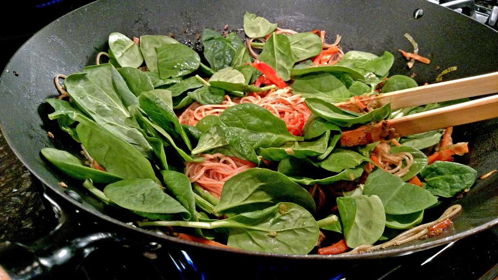 spinach cooking in wok with pasta and vegetables