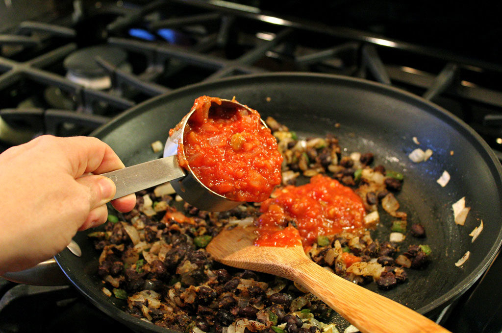 pouring salsa into the pan