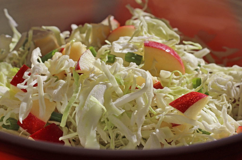 close up photo of chopped cabbage apples & green onions