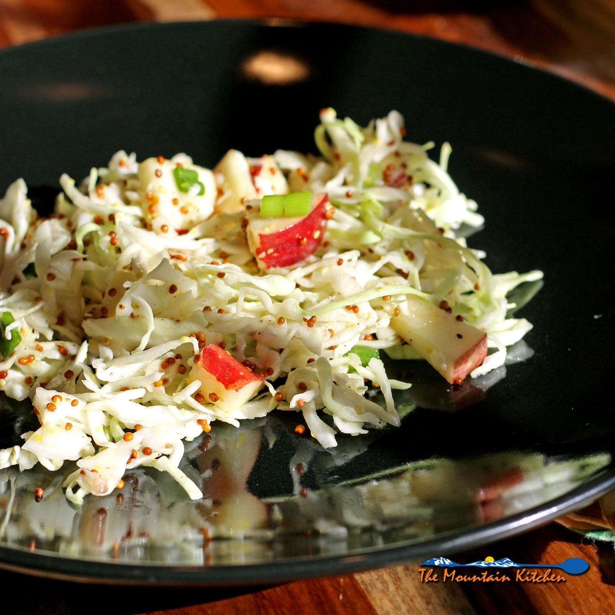 Apple-Cabbage Slaw with crunchy cabbage, crisp apples, and green onions tossed with a zesty mustard dressing, this colorful slaw makes a great side dish for any barbecue this summer.