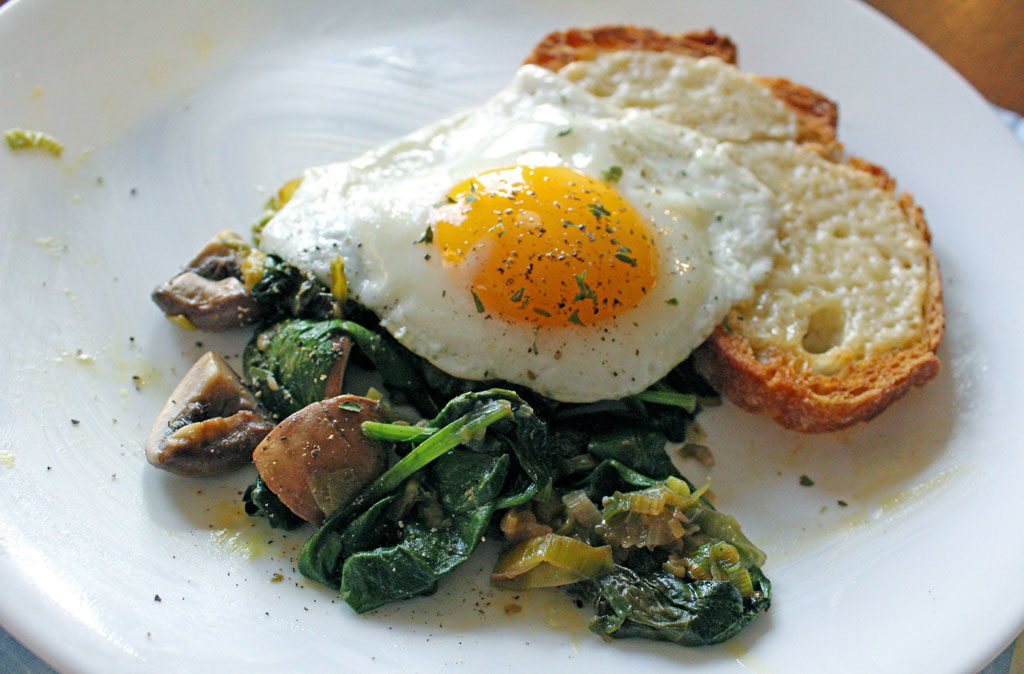 Leeks and Mushrooms With Cheesy Toasts and Fried Eggs on a plate