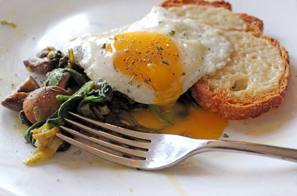 leeks mushrooms with toast and fried eggs with broken yolk