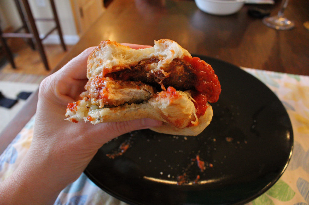 hand with bite taken out of chicken parmesan sub sandwiches