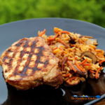 Grilled teriyaki pork chop on plate with rice and vegetables