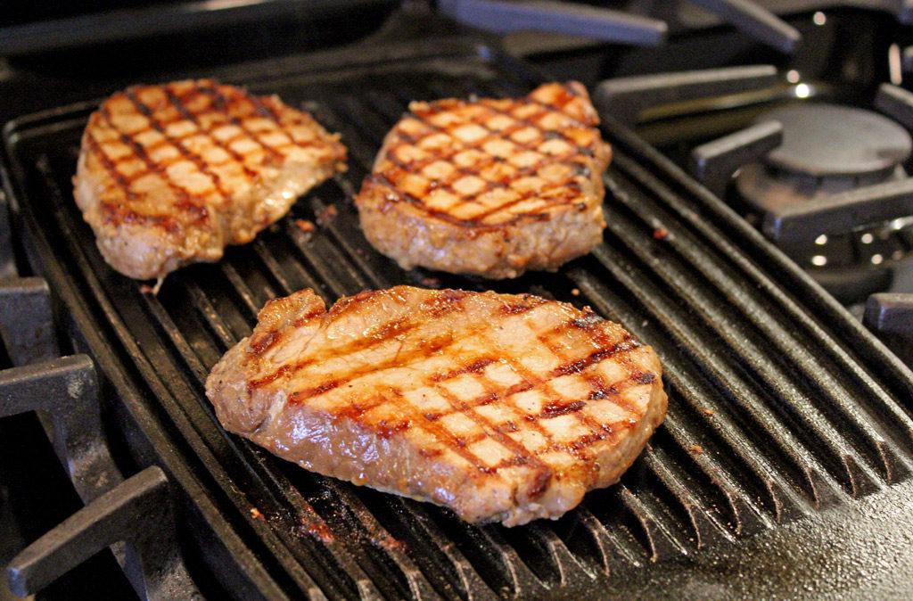 pork chops grilling on stove