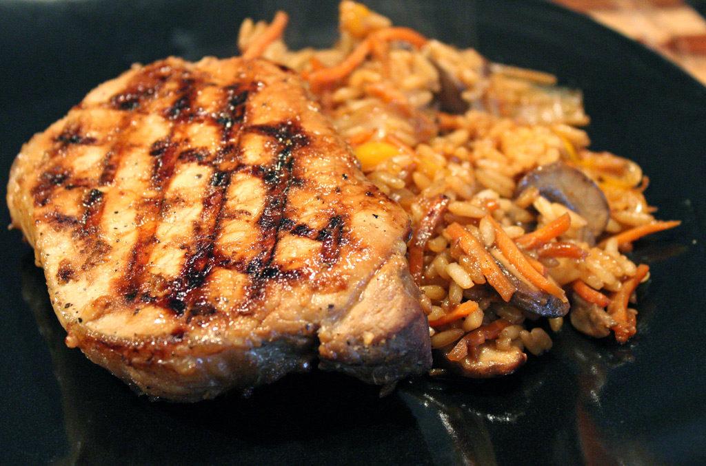 grilled teriyaki pork chop on plate with rice and veggies
