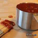 classic barbecue sauce in measuring cup with messy basting brush