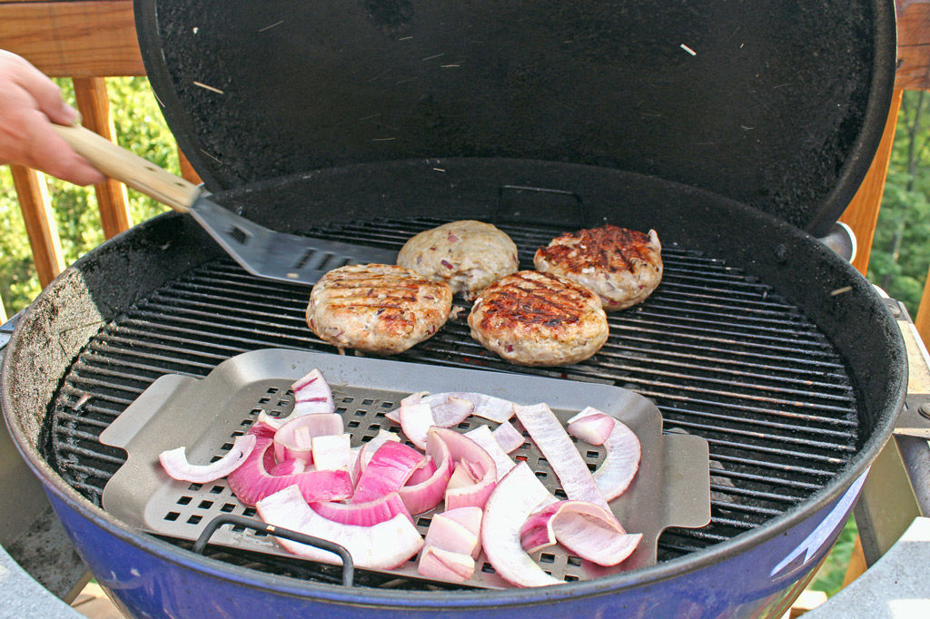 flipping burgers on grill with onions