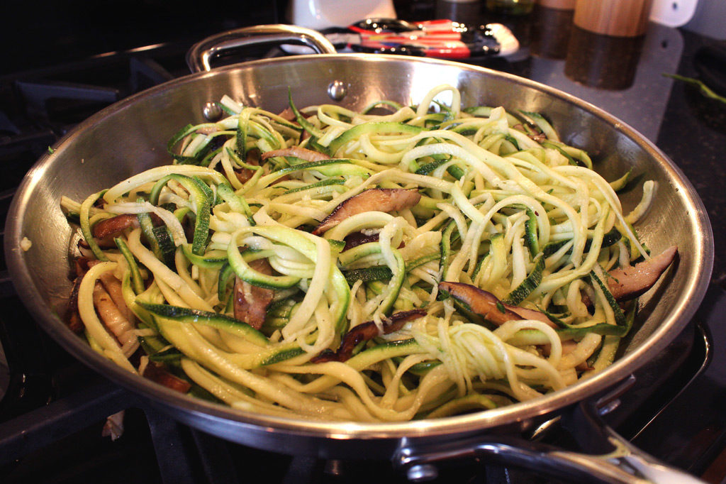 mushrooms and zucchini noodles cooking in pan
