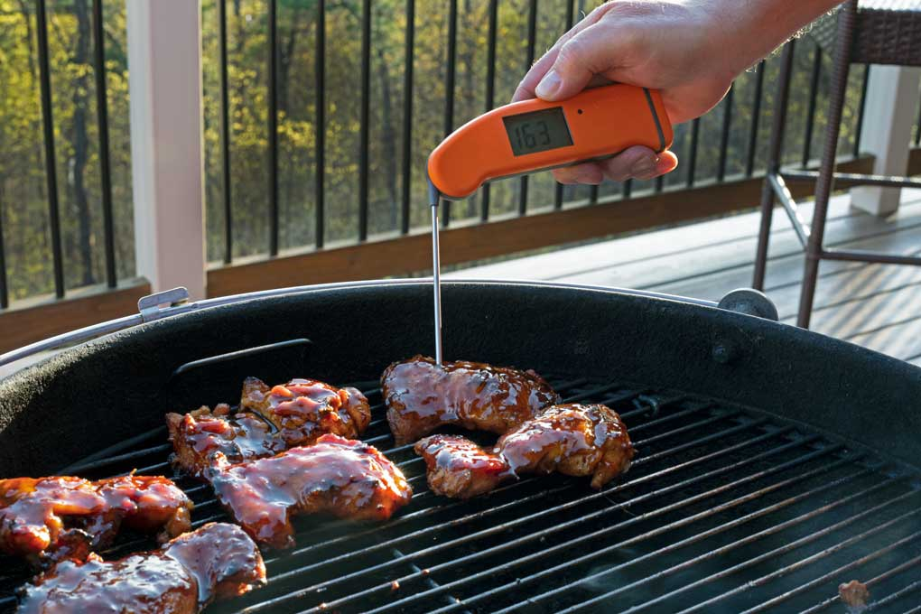 checking temperature of chicken with instant-read thermometer