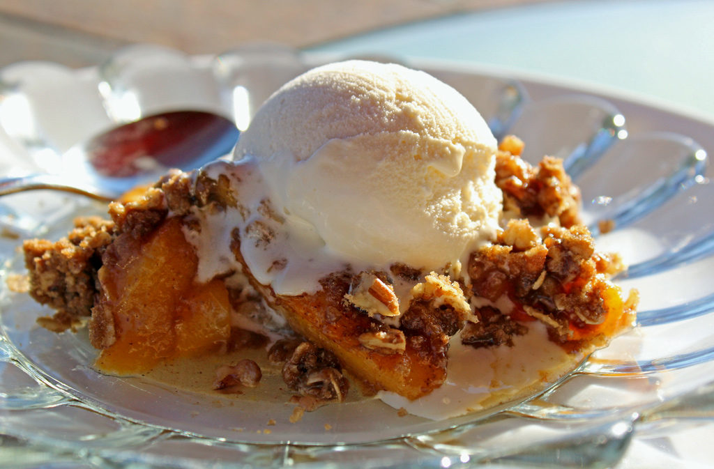 This cinnamon peach crisp is made of ripe juicy peaches tossed in sugar and cinnamon with a comforting topping of crunchy rolled oats, brown sugar, pecans, and butter with the warmth of more cinnamon, nutmeg and ginger. | TheMountainKitchen.com