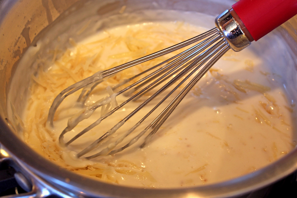 whisking cheese sauce