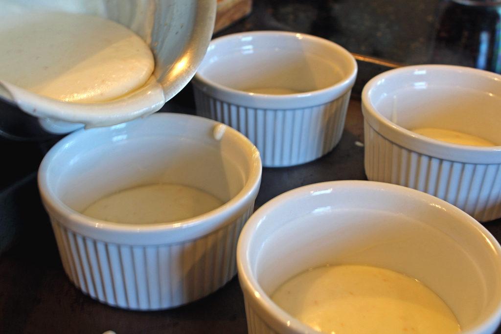 pouring cheese sauce in ramekins