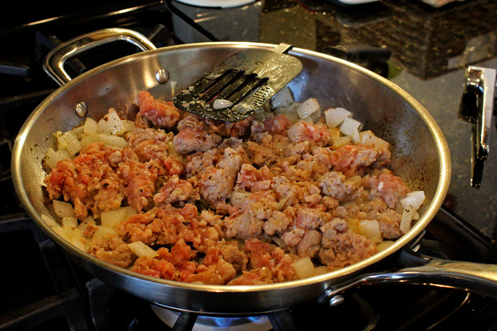 sausage and onions cooking in a pan