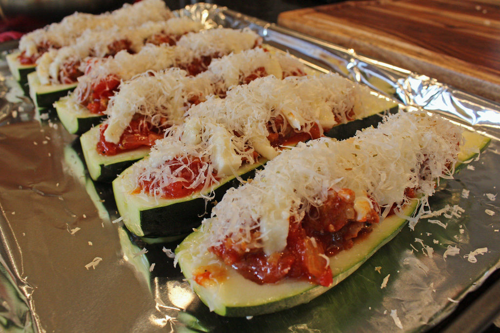 These Sweet Italian Sausage Stuffed Zucchini Boats are made with garden-fresh zucchini stuffed with mozzarella cheese and sweet Italian sausage mixed with diced tomatoes and herbs, piled high with even more cheese!   TheMountainKitchen.com