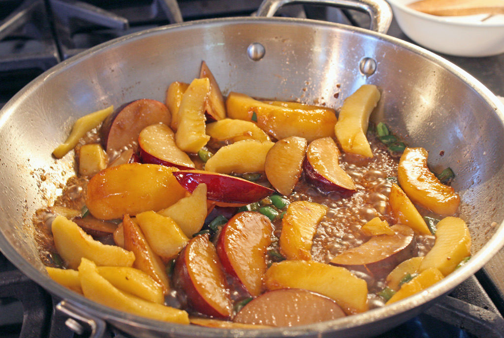 plums and peaches cooking in pan