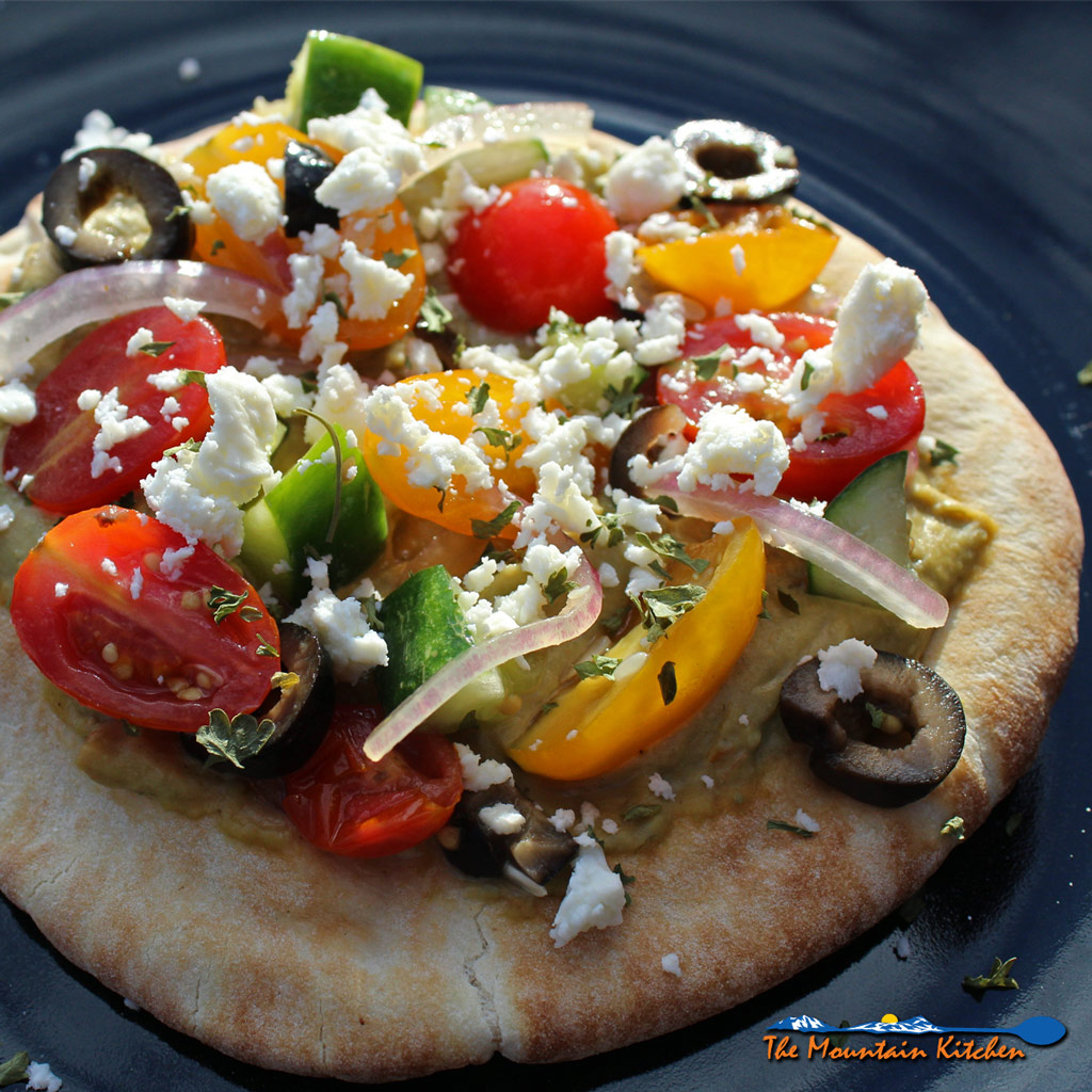 These No-Bake Greek Pizzas are made with pita bread topped with hummus, Greek salad and feta cheese. A really quick easy and healthy Meatless meal.