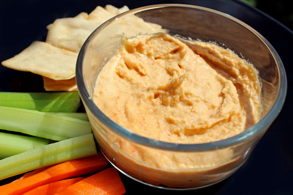 roasted red pepper hummus in bowl with veggies