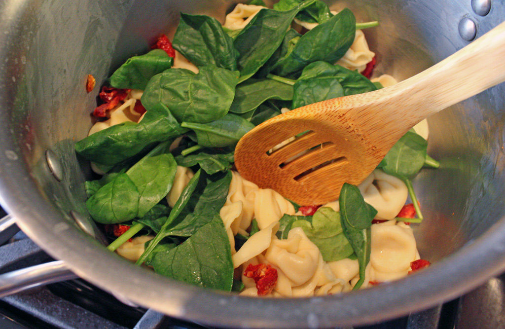 stirring spinach, tortellini and sun-dried tomatoes in pot