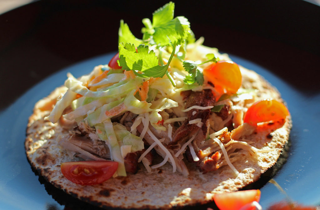 Applewood Smoked Pork Carnitas with Spicy Cabbage Slaw served on a tortilla on black plate