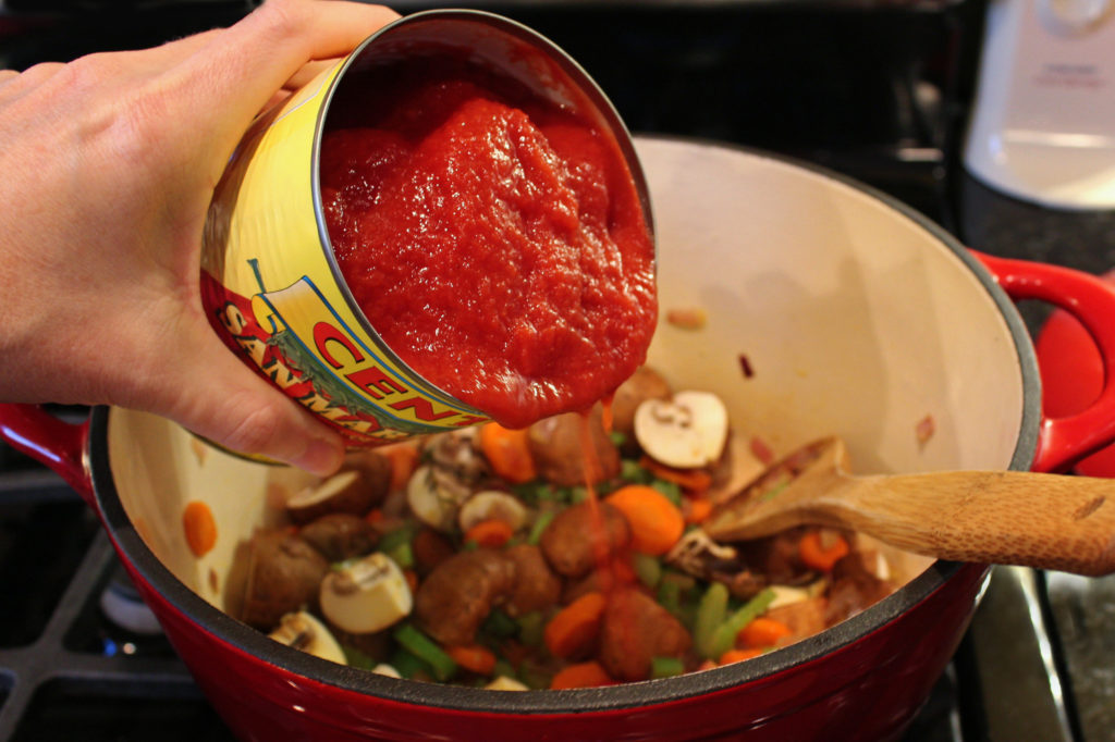 Pouring canned tomatoes into pot with vegetables