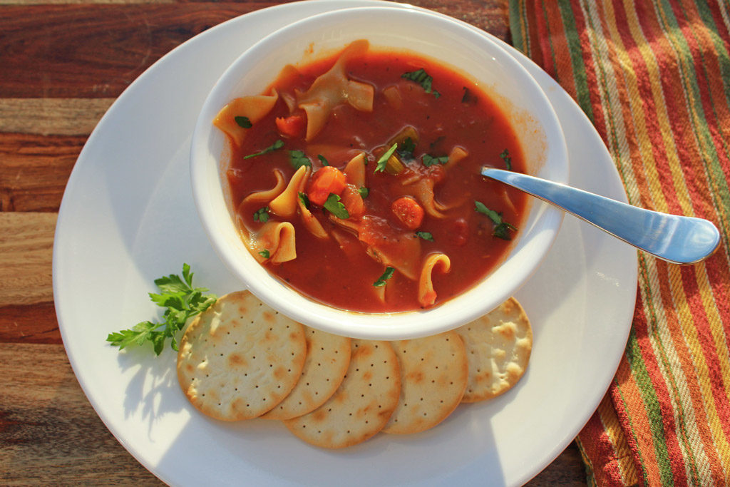 vegetable noodle soup in bowl with crackers on a plate